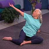 woman with white hair sitting on floor doing yoga pose